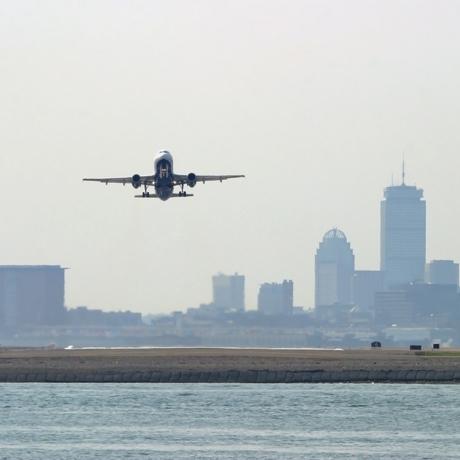 Aircraft departing Boston's Logan International Airport.  Boston skyline in background.