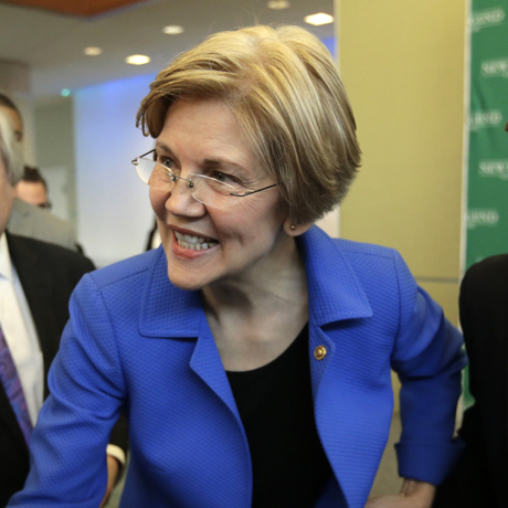U.S. Sen. Elizabeth Warren, D-Mass., center, greets business leaders during a New England Council luncheon at a hotel, Monday, March 27, 2017, in Boston. Larry Zabar, New England Council executive vice president, second from left, looks on. (AP Photo/Steven Senne)