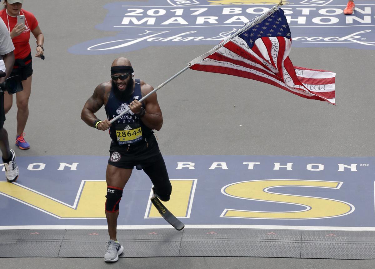 Jose Sanchez, of San Antonio, carries the United States flag across the finish line in the 121st Boston Marathon on Monday, April 17, 2017, in Boston. (AP Photo/Charles Krupa)