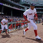 FILE - In this April 3, 2017, file photo, Boston Red Sox players including Mookie Betts, middle, take the field for the start of their baseball home opener against the Pittsburgh Pirates, at Fenway Parkin Boston. The Red Sox have fumigated and disinfected their clubhouse at Fenway Park to help fight the flu.Boston manager John Farrell says it has been done a few times while the team has been on the road. The Red Sox have been hit hard by the bug. Hanley Ramirez has played just two games because of it, and Mookie Betts returned to the lineup Sunday after the flu kept him out for almost a week. (AP Photo/Elise Amendola, File)