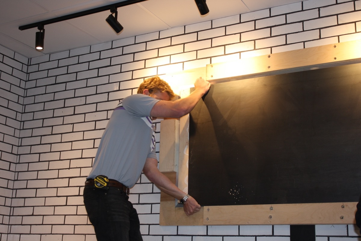 A contractor with Cafco Construction Management installs Blackbird Doughnuts' new chalkboard menu in Fenway. / Photos by Jacqueline Cain