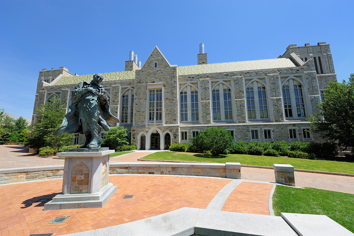 The Saint Ignatius Loyola statue in front of a grand building on the Boston College campus