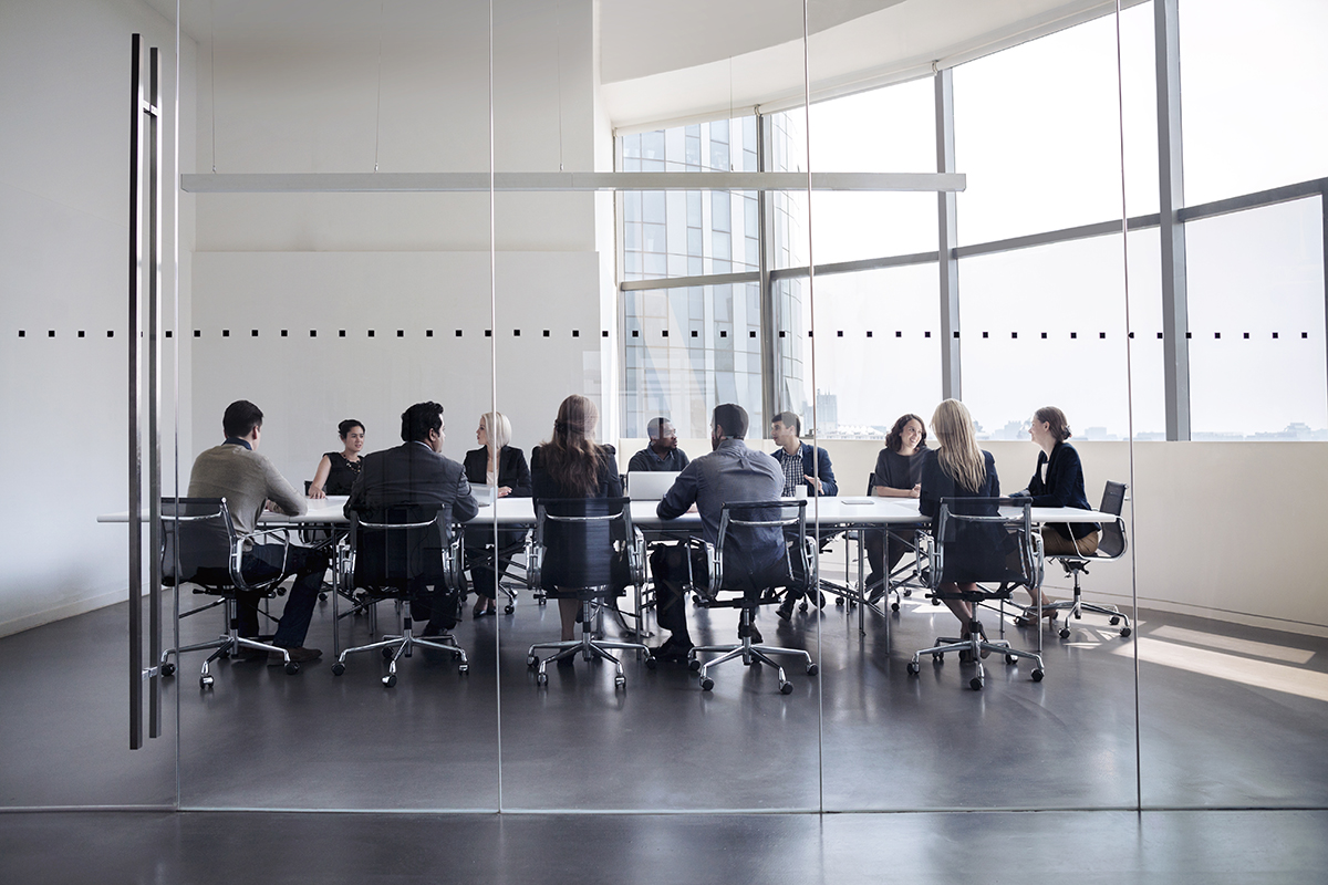 Men and women in suits sit at an office boardroom table