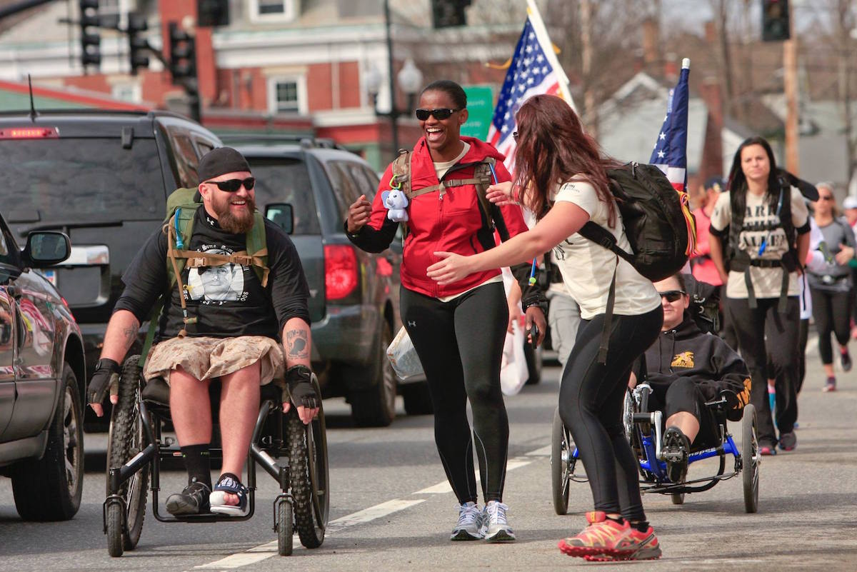 a man in a wheelchair and two walking women converse as they move forward
