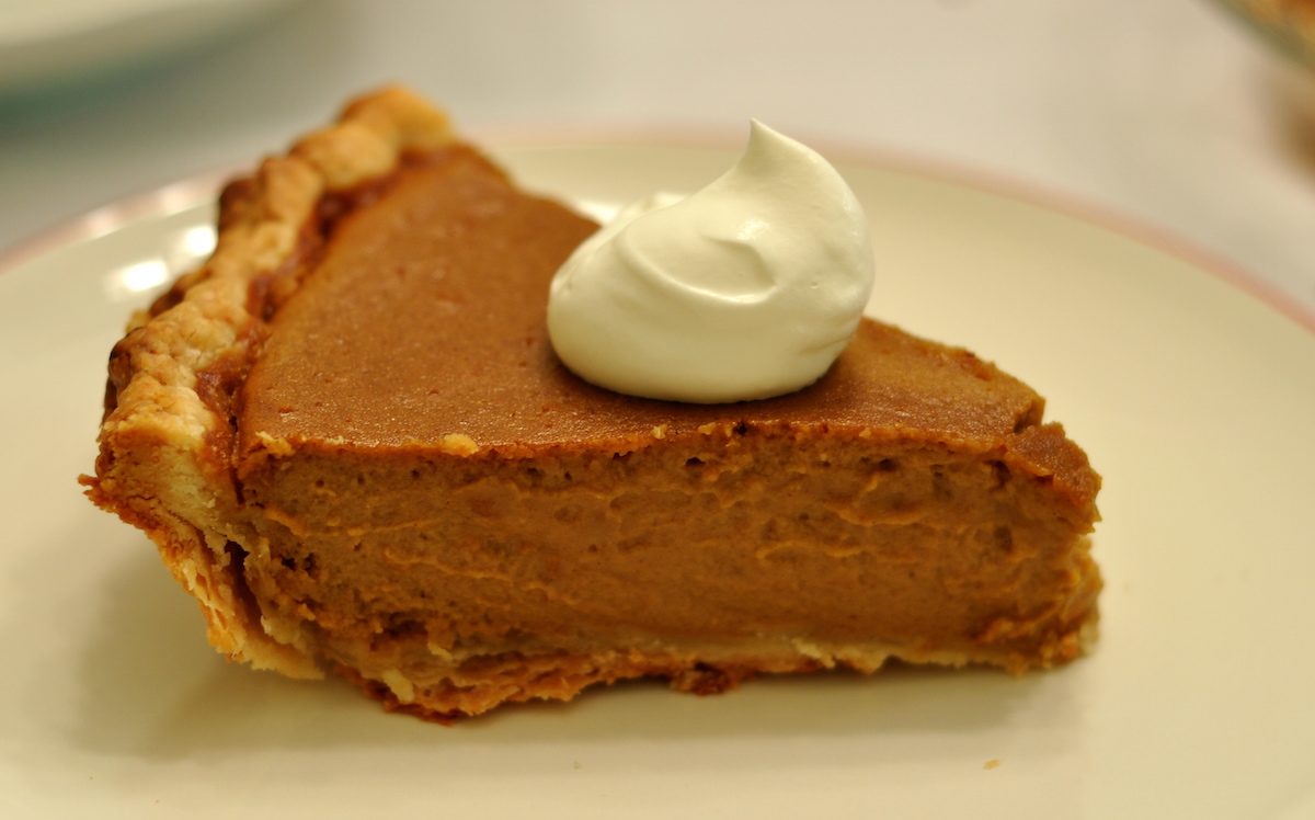 pumpkin pie slice with dollop of whipped cream