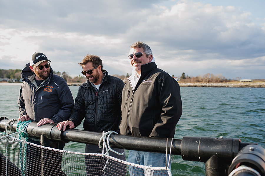 (L to R) Row 34 group purchaser Phil Peterson, UNH and N.H. Sea Grant aquaculture specialist Michael Chambers, and Row 34 chef/partner Jeremy Sewall on the floating platform of the steelhead trout farm
