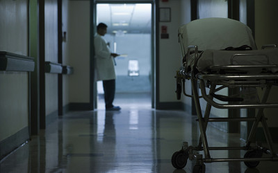 A doctor at the end of a hospital corridor with a hospital bed in the foreground