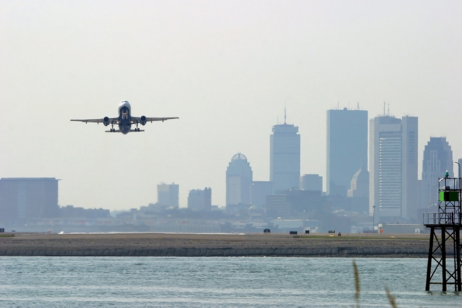 A plane leaves Boston Logan Airport with the city skyline in the background