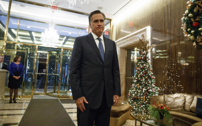 Mitt Romney stands next to a Christmas tree forwning