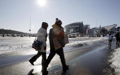 Bundled up fans walk an icy path toward Gillette Stadium