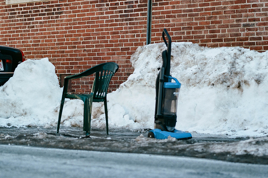 A lawn chair and vacuum cleaner in shoveled-out parking spots
