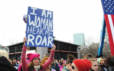 """A woman holding a poster that says """"I am woman, hear me roar"""""""